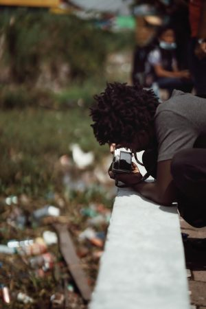 Kid taking pictures of Global Warming and plastic waste effects in Suriname